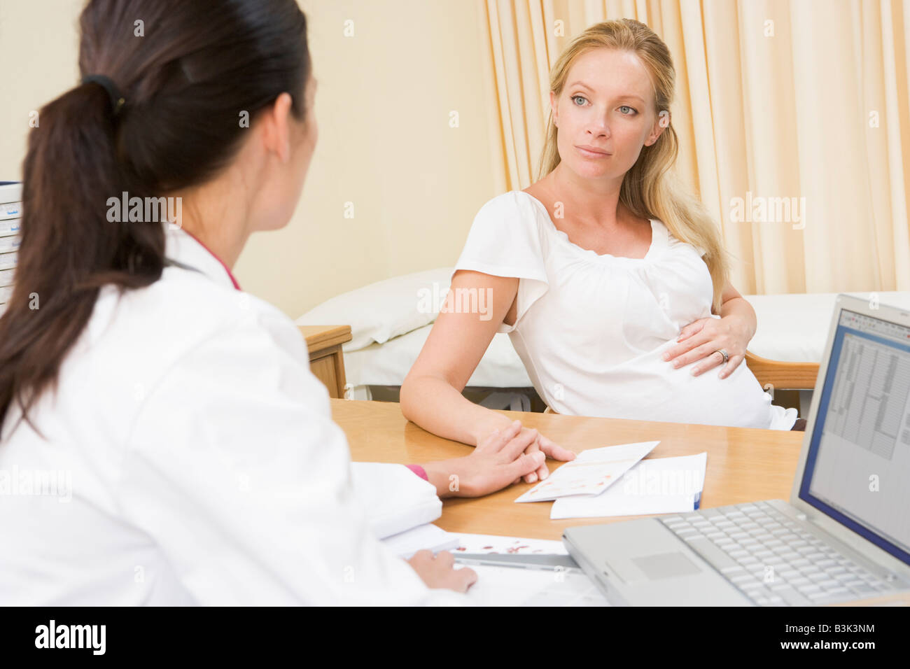 Doctor with laptop and pregnant woman in doctor's office - Stock Image
