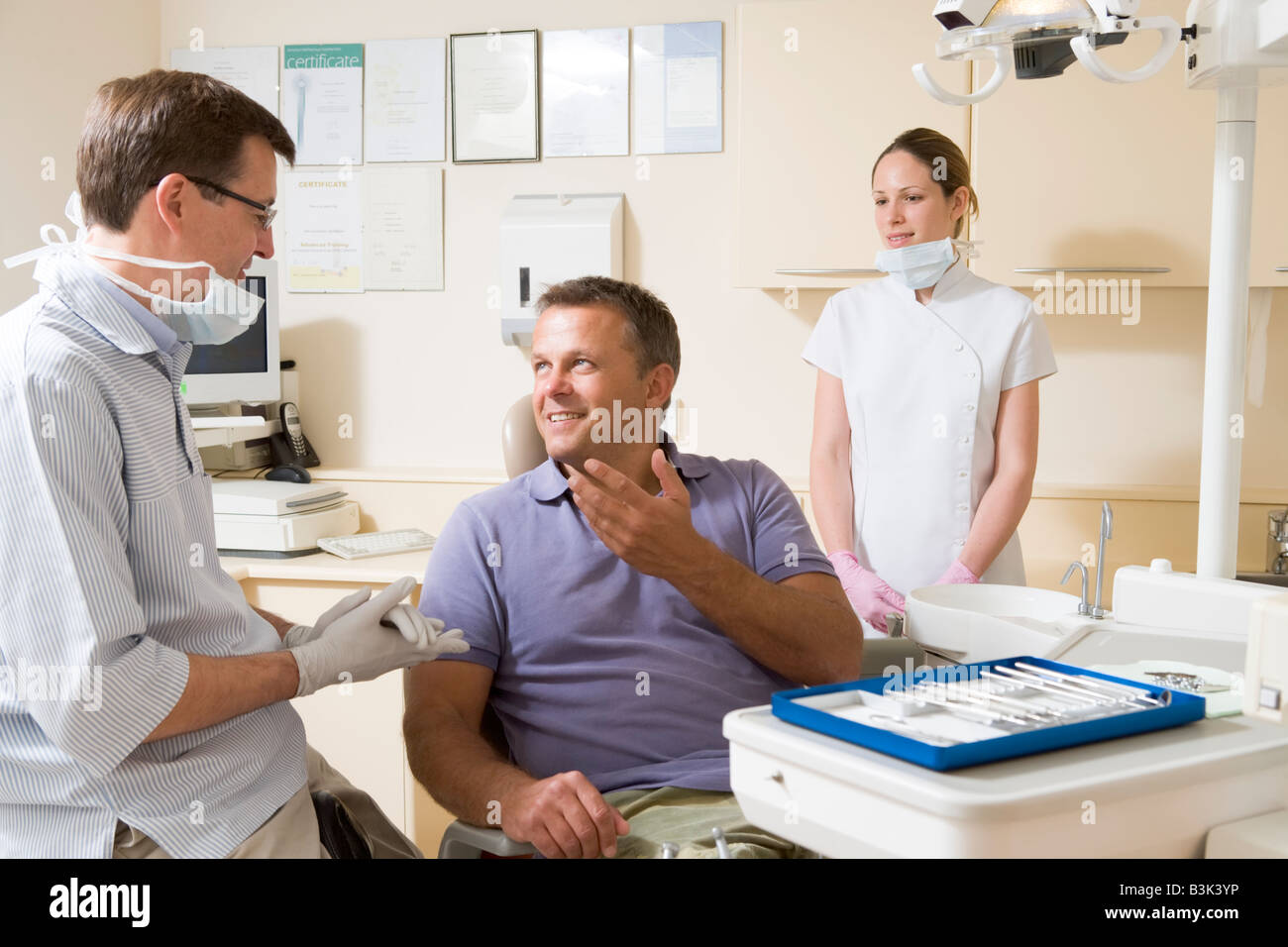 Dentist and assistant in exam room with man in chair smiling - Stock Image