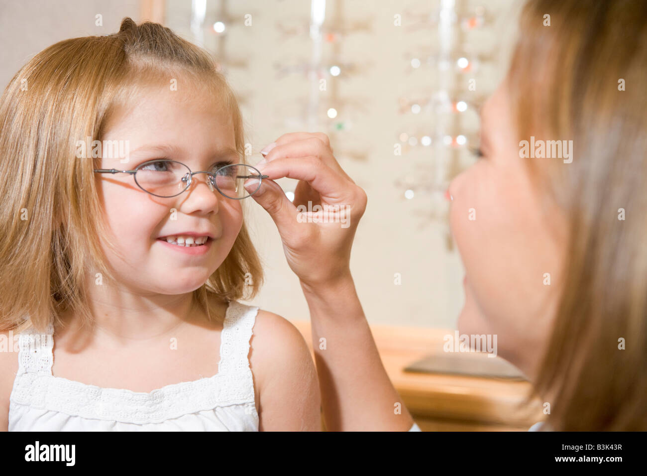 Woman trying eyeglasses on young girl at optometrists smiling - Stock Image