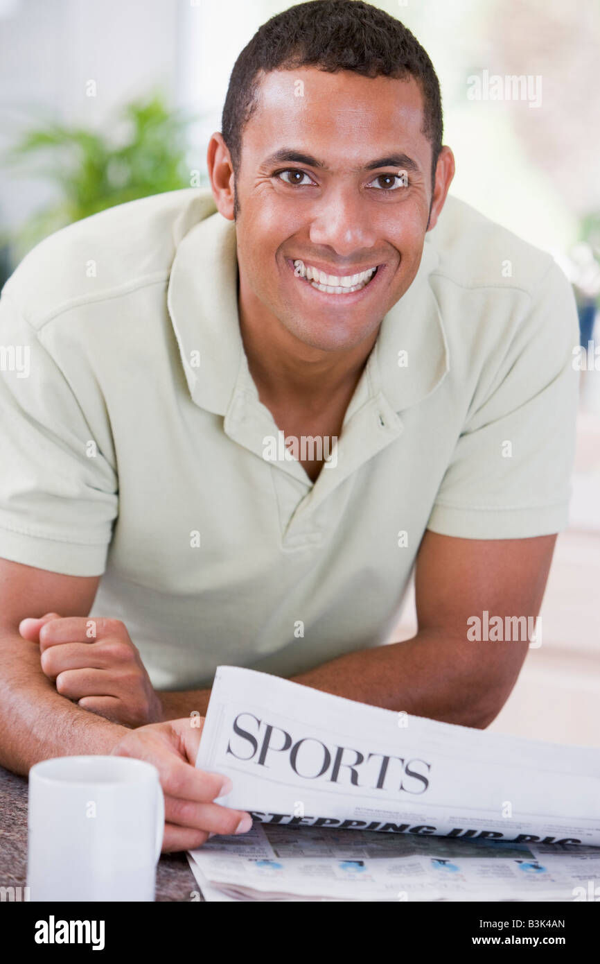 Man in kitchen reading newspaper and smiling - Stock Image