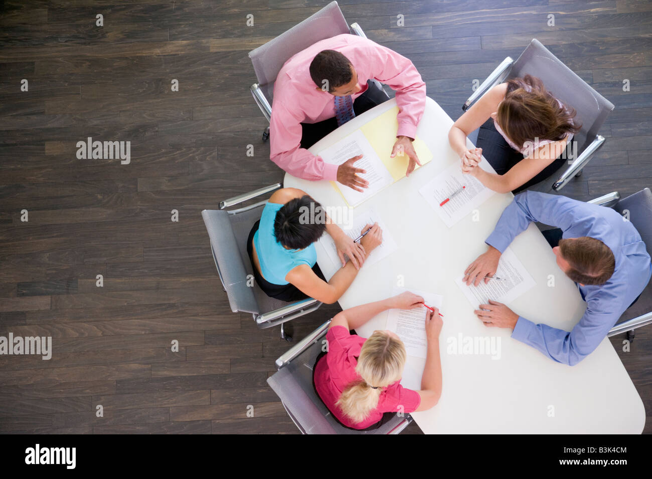 Five businesspeople at boardroom table - Stock Image