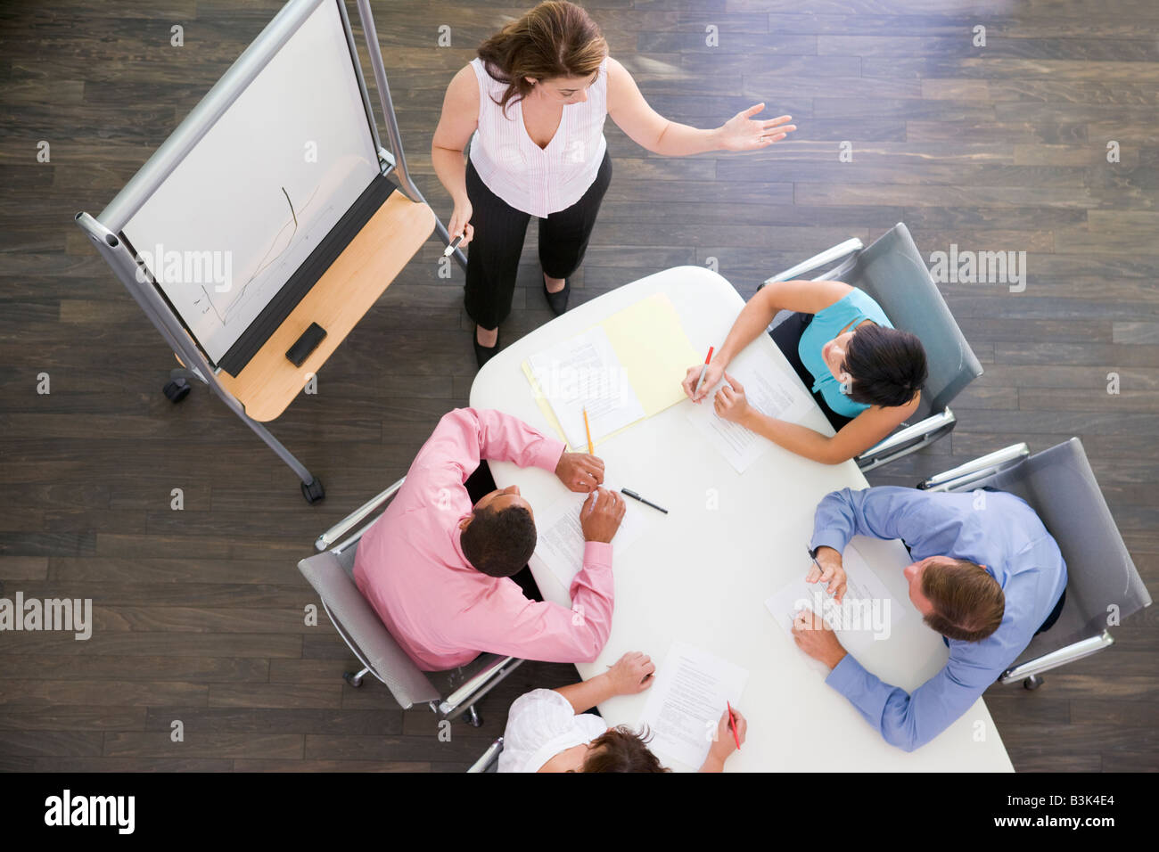 Four businesspeople at boardroom table watching presentation - Stock Image