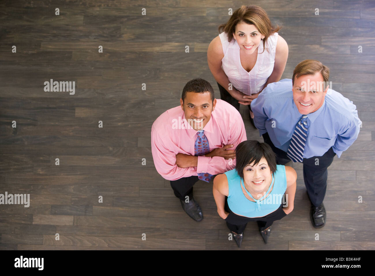 Four businesspeople standing indoors smiling - Stock Image