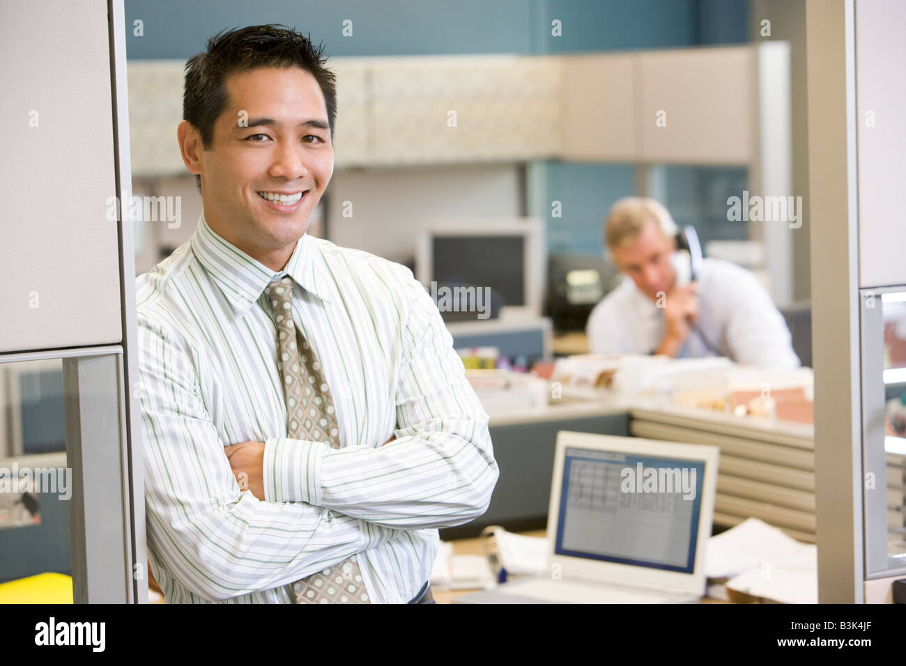 Businessman standing in cubicle smiling - Stock Image