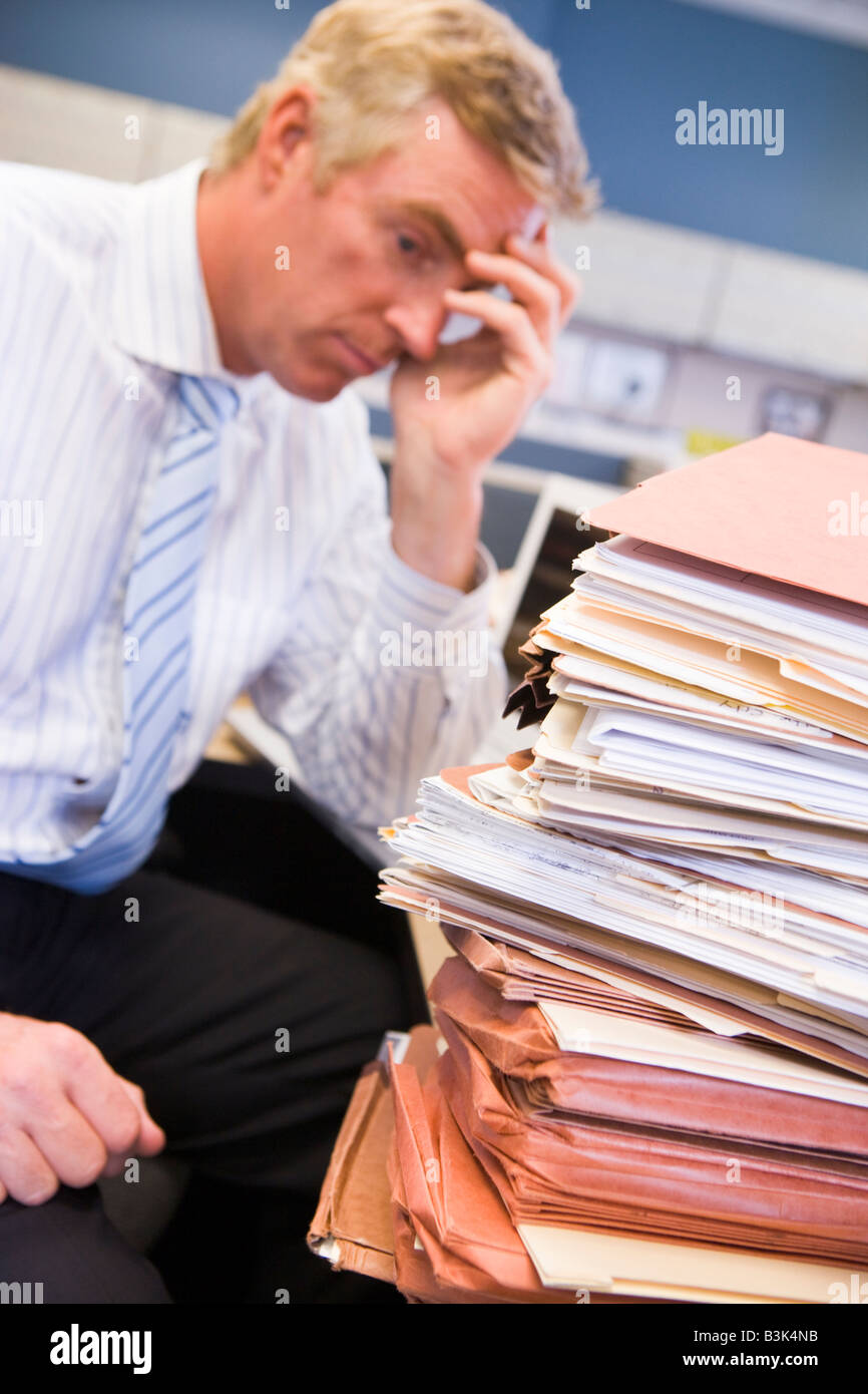 Businessman in cubicle with laptop and stacks of files - Stock Image
