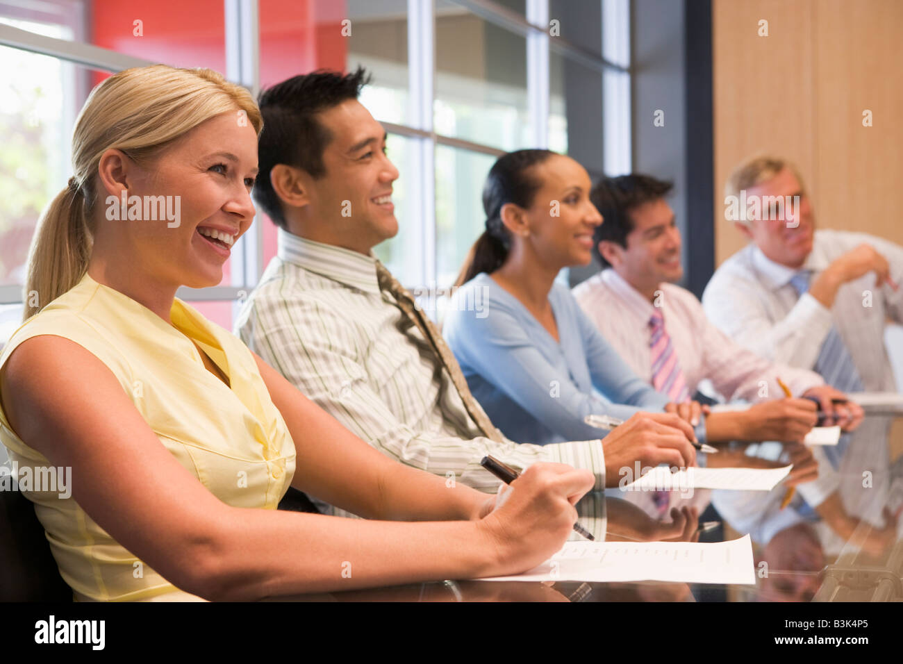 Five businesspeople at boardroom table smiling - Stock Image