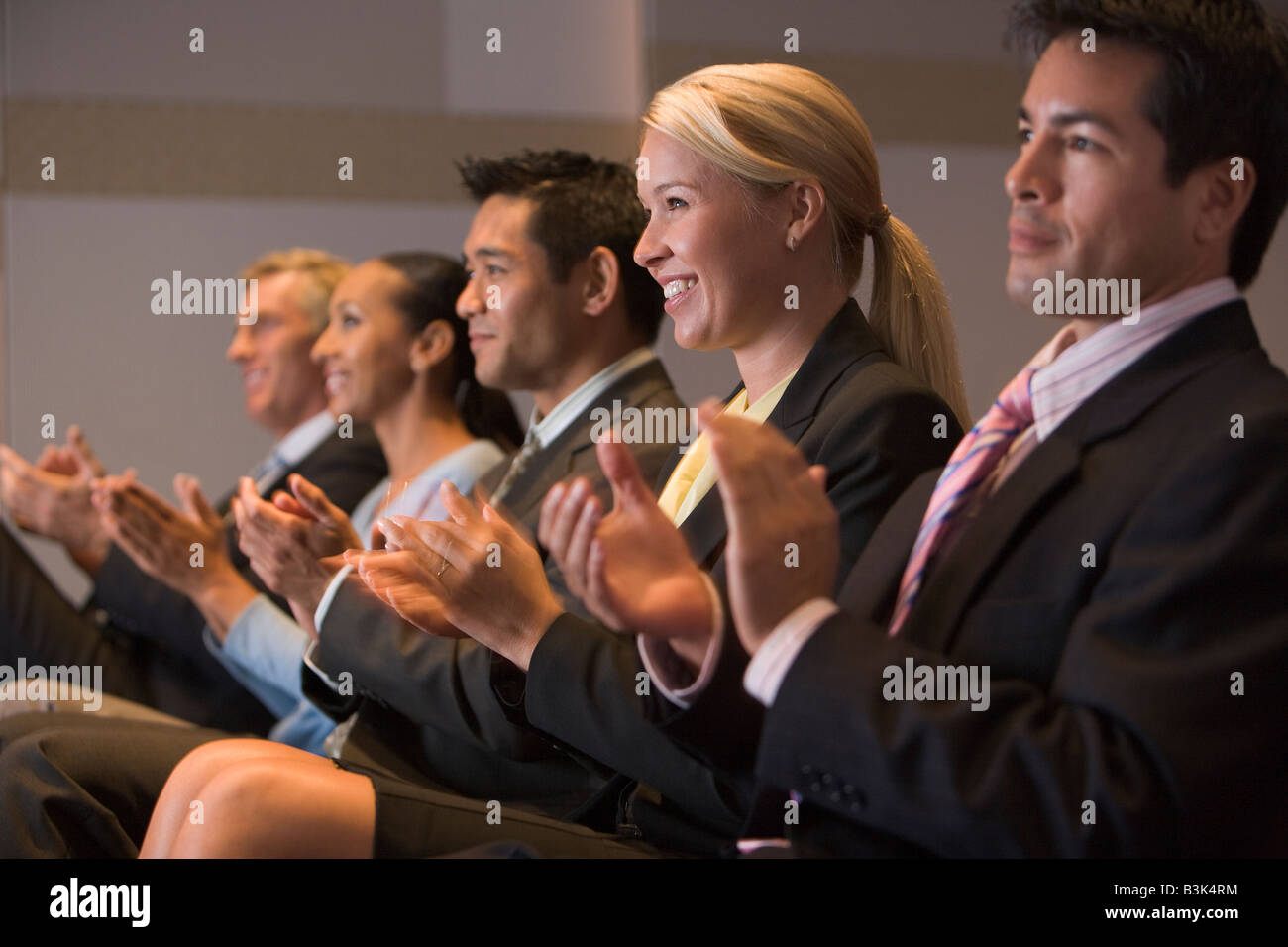 Five businesspeople applauding and smiling in presentation room - Stock Image