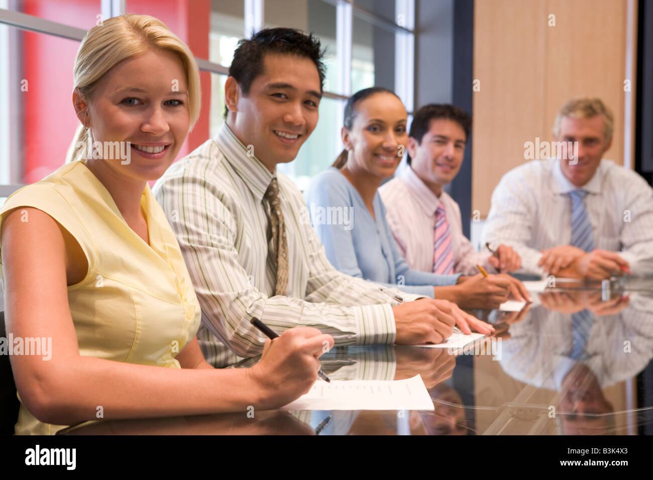 Five businesspeople in boardroom smiling - Stock Image