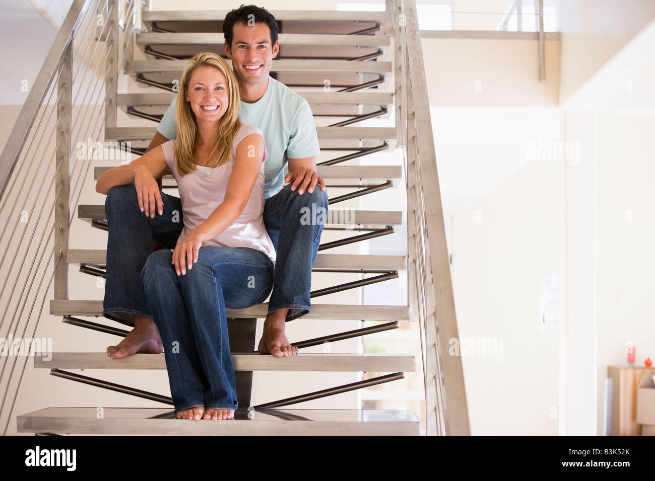 Couple sitting on staircase smiling - Stock Image