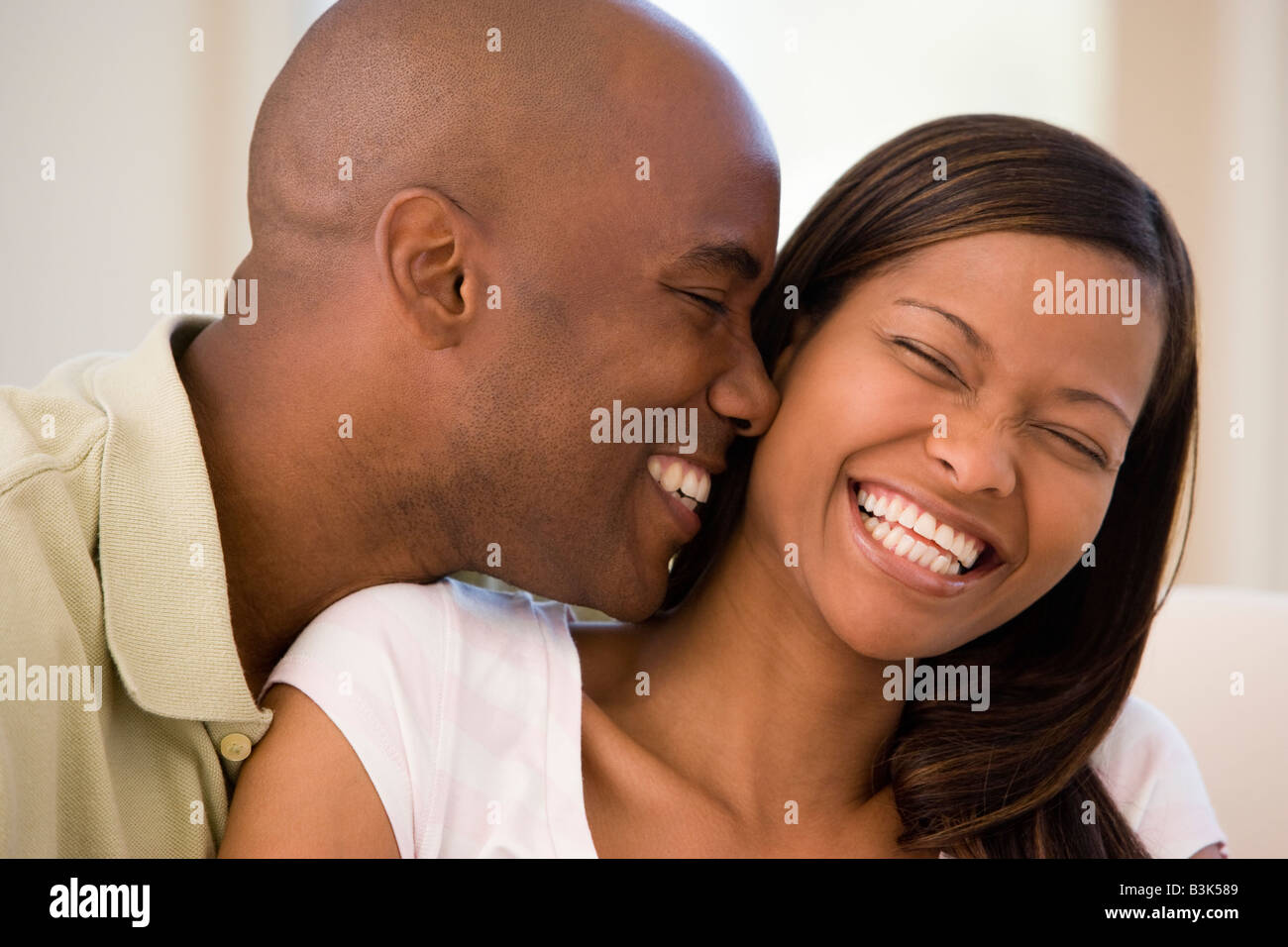 Couple in living room smiling - Stock Image