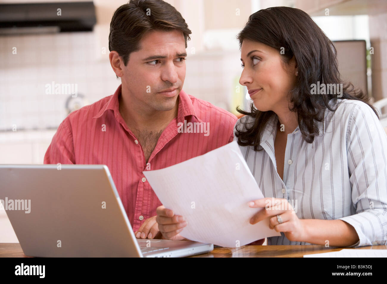 Couple in kitchen with paperwork using laptop looking unhappy - Stock Image