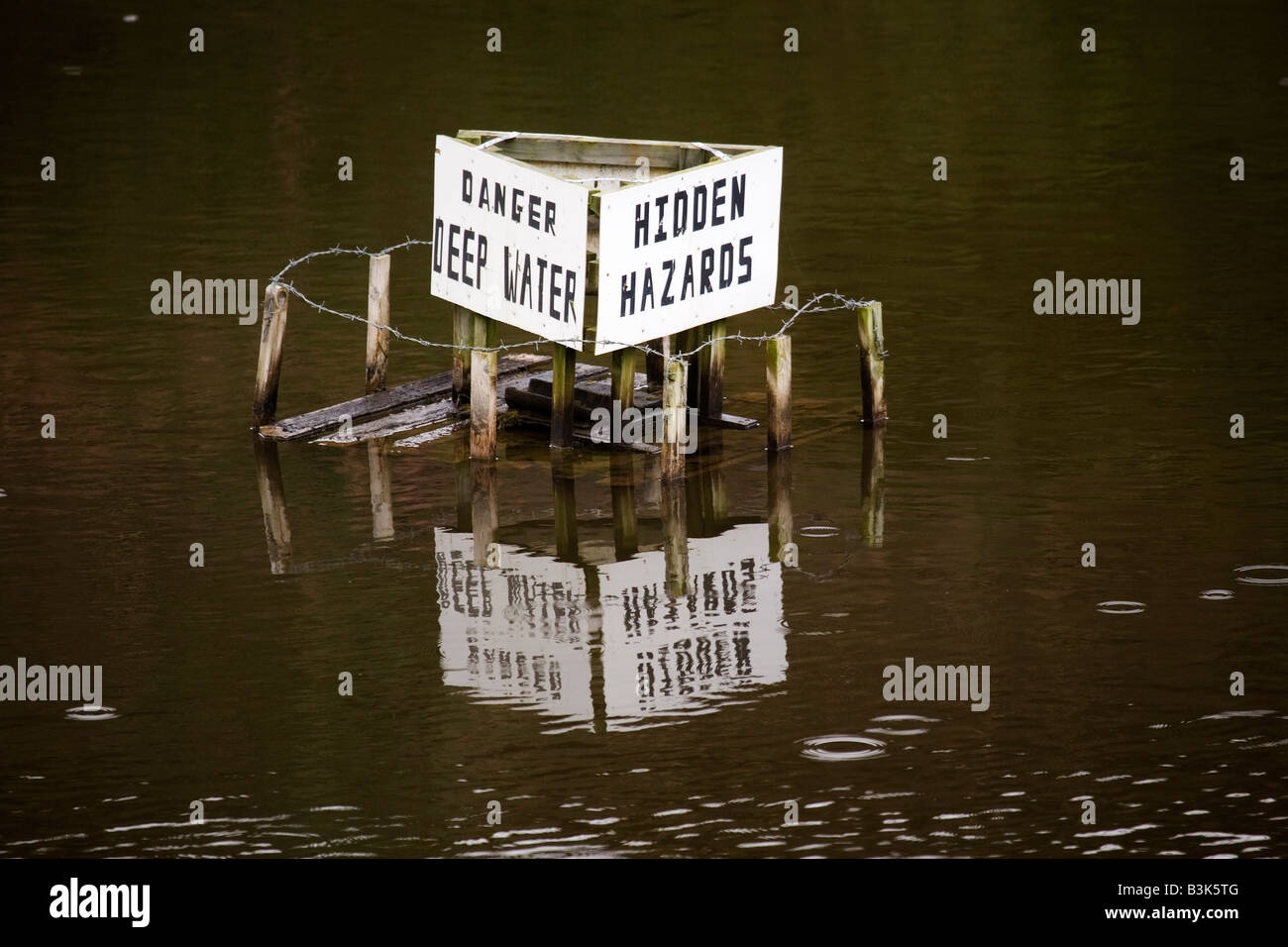 A sign in a quarry in County Durham, England, warns of deep water and hidden hazards. - Stock Image