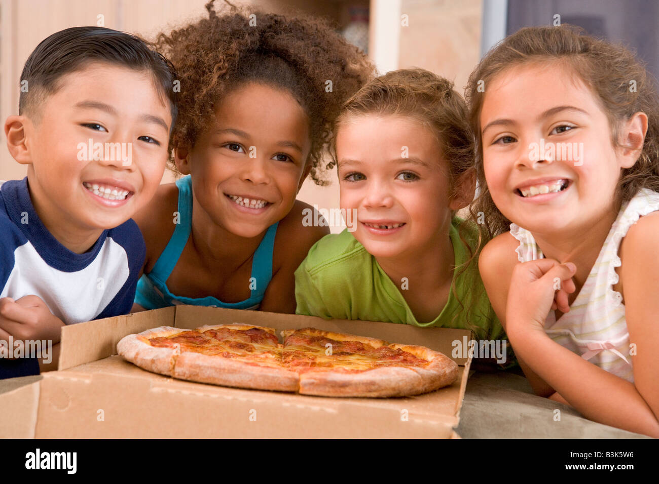Four young children indoors with pizza smiling - Stock Image