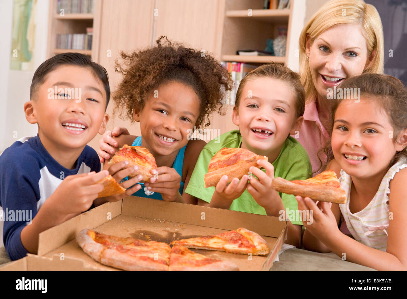 Four young children indoors with woman eating pizza smiling - Stock Image