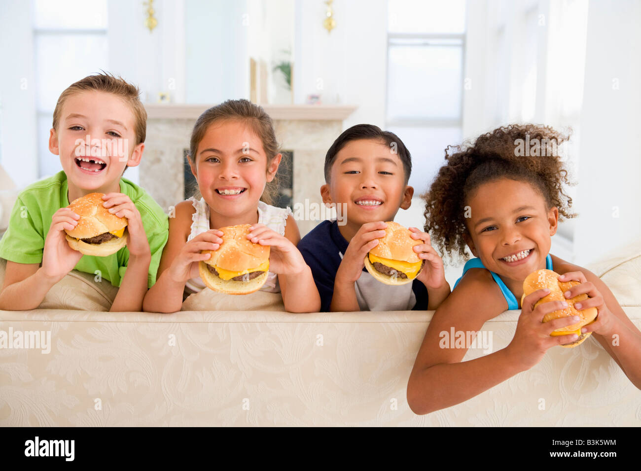 Four young children eating cheeseburgers in living room smiling - Stock Image