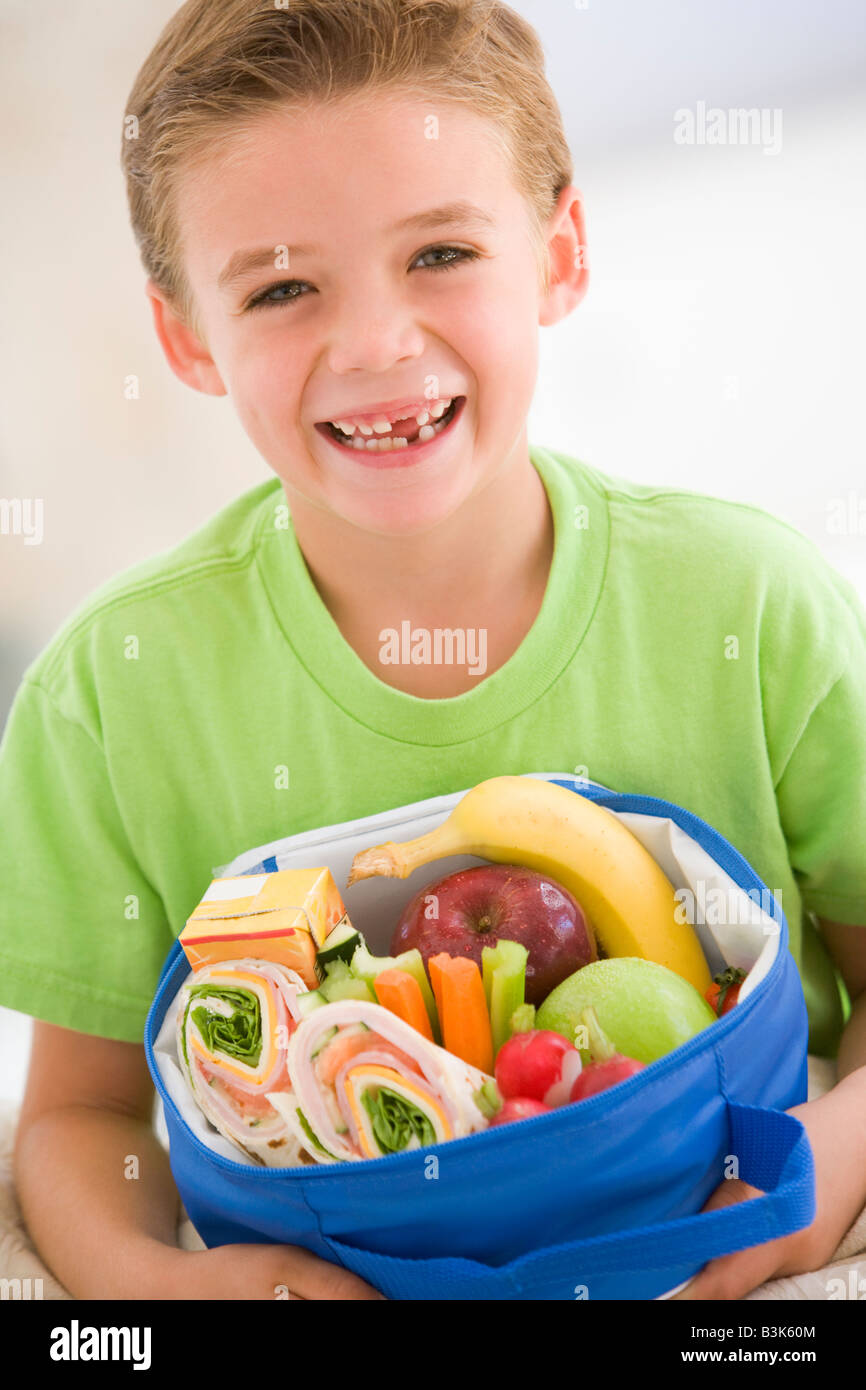 Young boy holding packed lunch in living room smiling - Stock Image