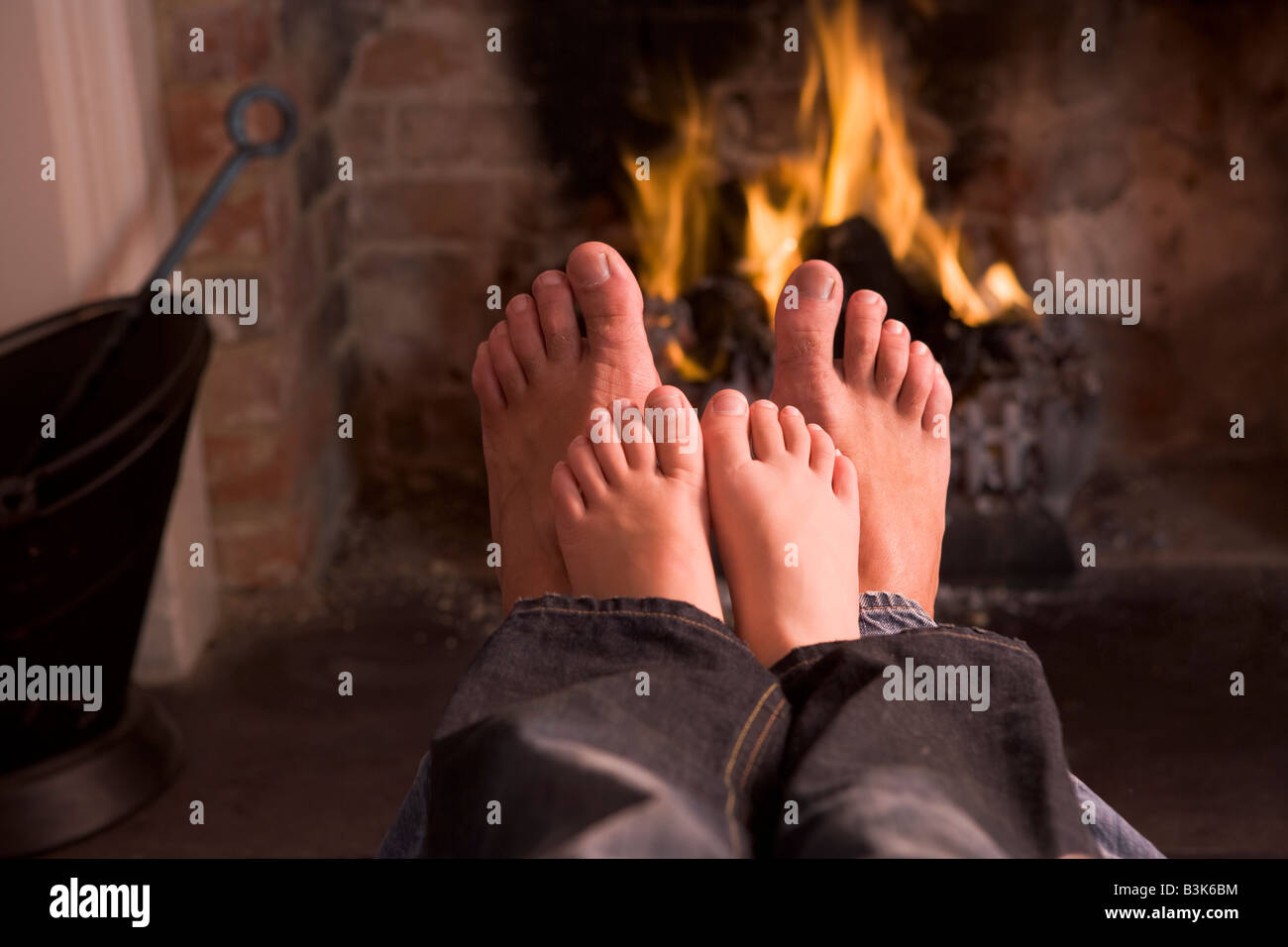 Father and son's Feet warming at a fireplace - Stock Image