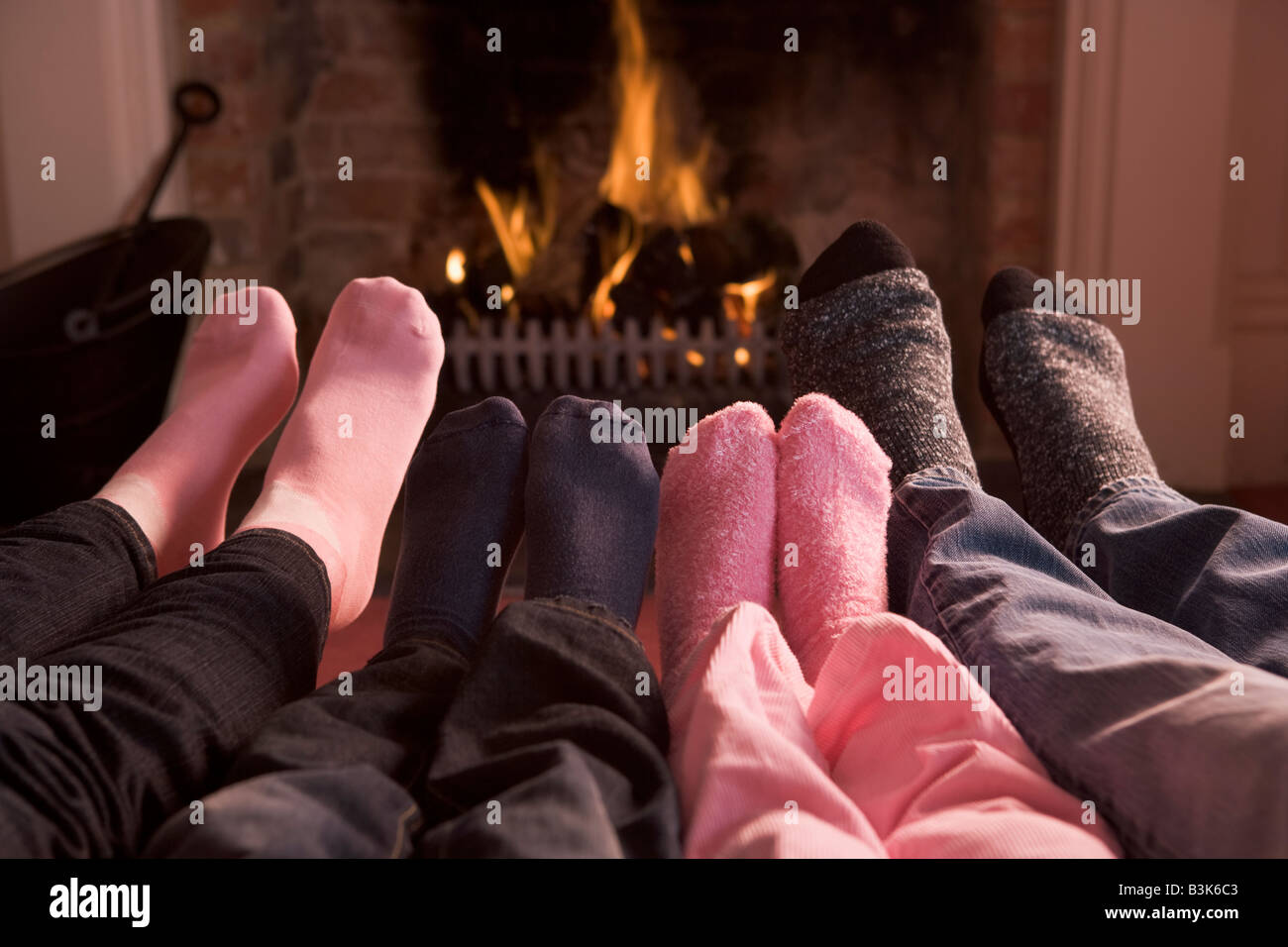 Family of Feet warming at a fireplace - Stock Image