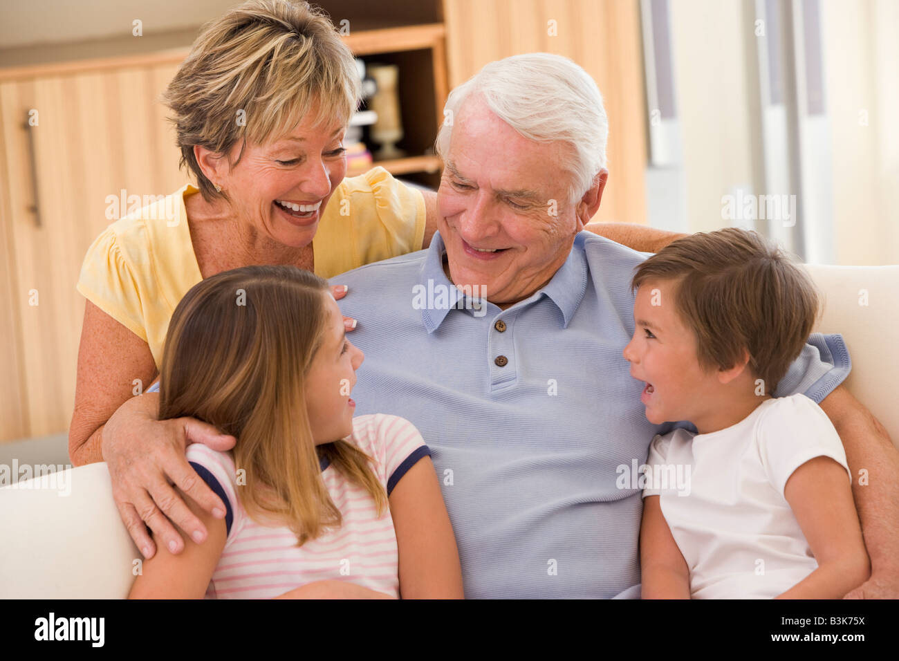 Grandparents laughing with grandchildren. - Stock Image