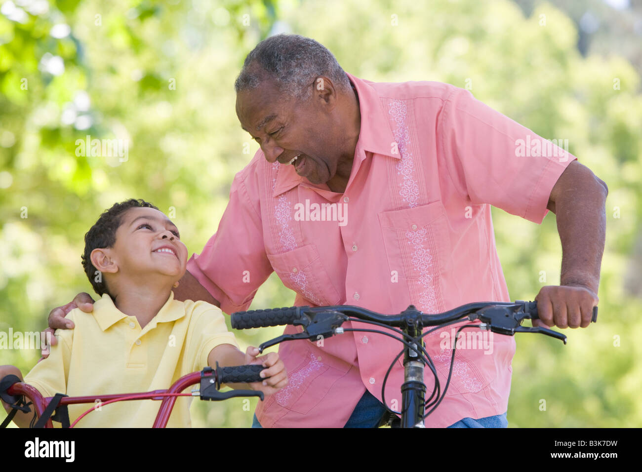 Grandfather and grandson on bikes outdoors smiling - Stock Image