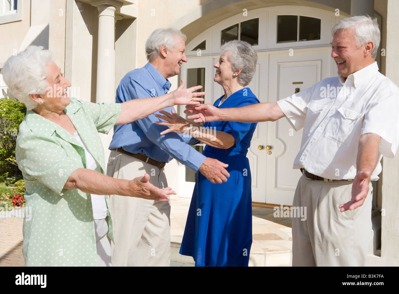 Two senior couples greeting each other with open arms Stock Photo