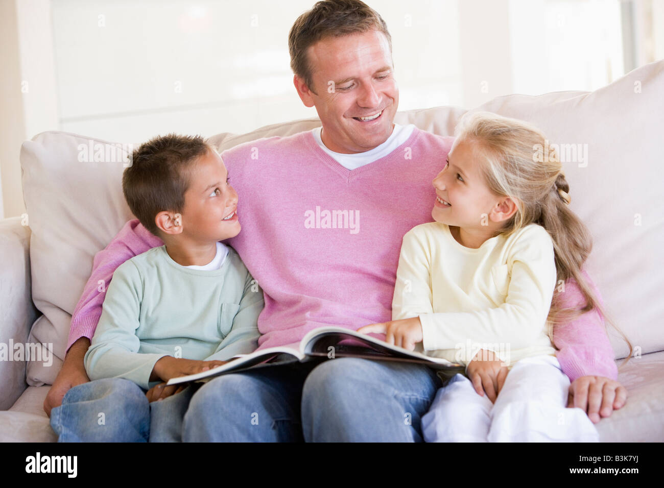 Man and two children sitting in living room reading book and smiling - Stock Image