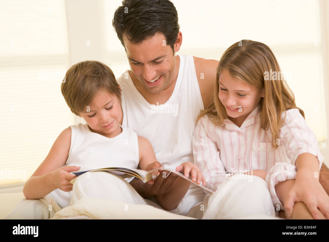 Man with two young children sitting in bed reading a book and smiling - Stock Image