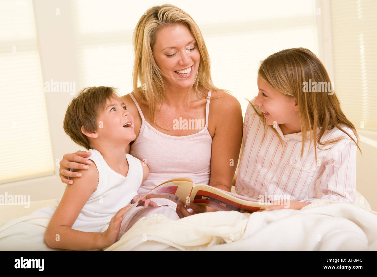 Woman with two young children sitting in bed reading book and smiling - Stock Image