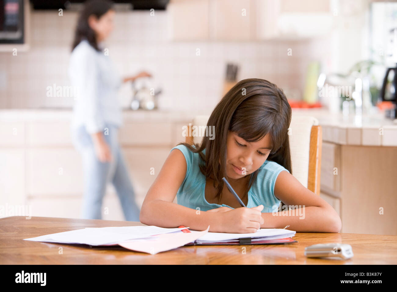 Young girl in kitchen doing homework with woman in background - Stock Image