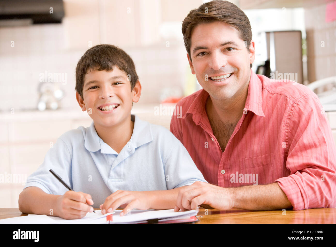 Man helping young boy in kitchen doing homework and smiling - Stock Image