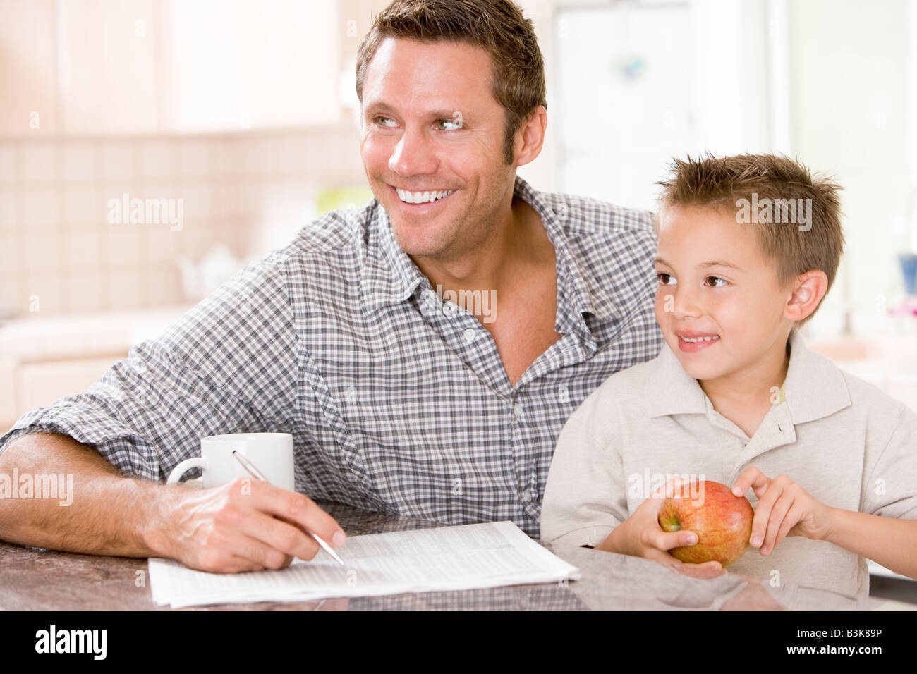 Man and young boy in kitchen with newspaper apple and coffee smiling - Stock Image