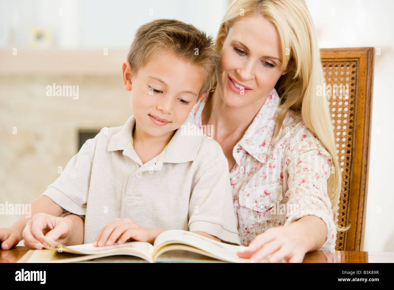 Woman and young boy reading book in dining room smiling - Stock Image