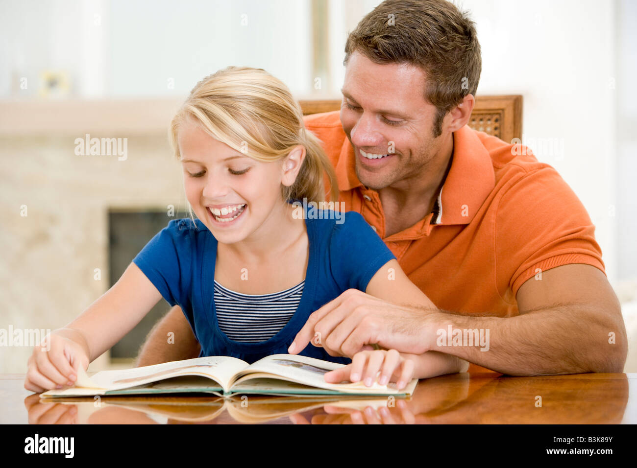 Man and young girl reading book in dining room smiling - Stock Image