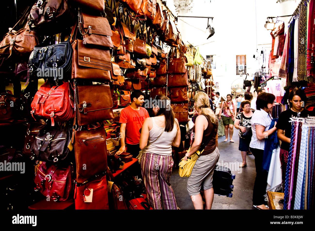 Shoppers looking at leather goods in a market in florence - Stock Image