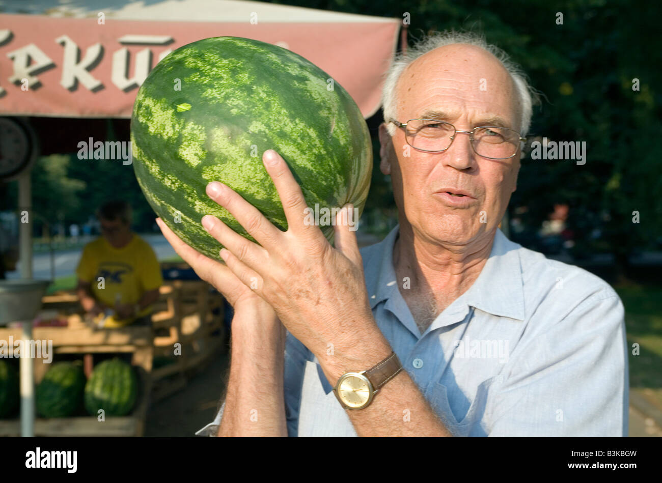 Elderly man with a watermelon just bought from a roadside grocer - Stock Image