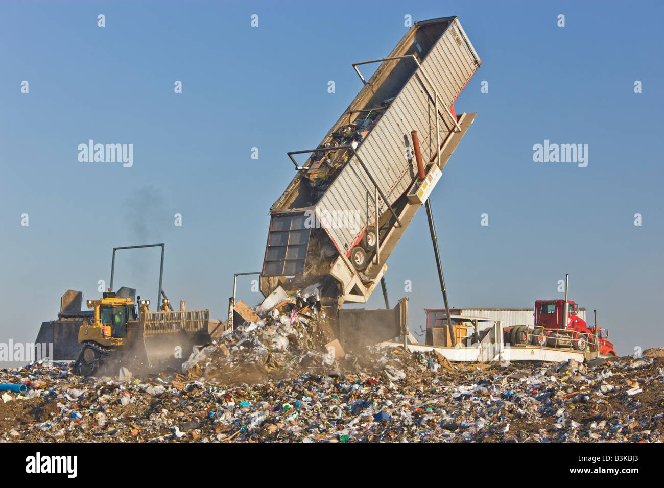 Tipper dumping semi trailer containing trash. - Stock Image