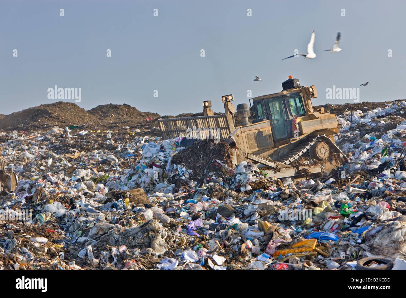 Tractor compactor/dozer pushing trash at landfill. - Stock Image