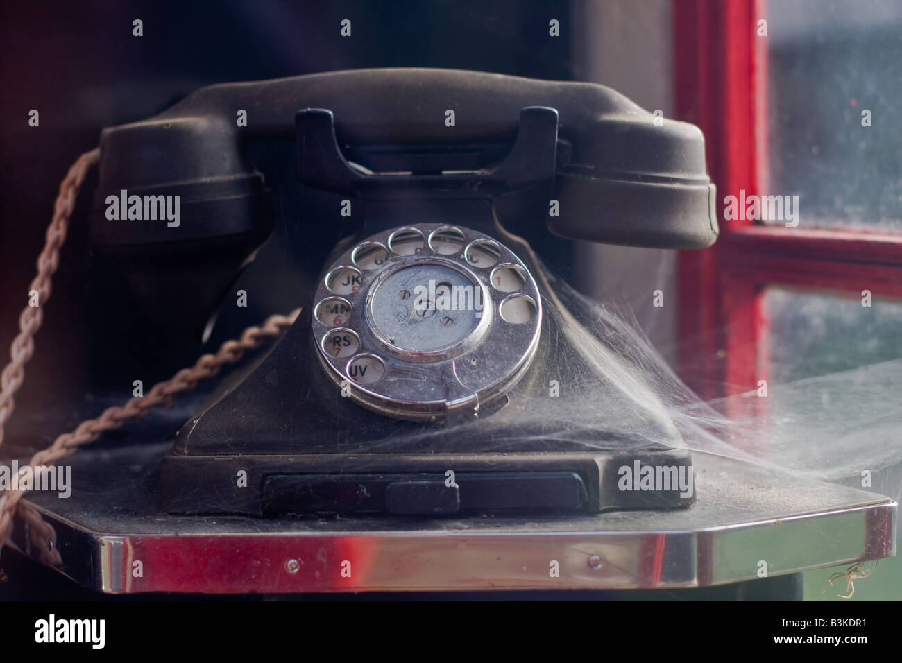 Bakelite old black type telephone with cobweb in old red telephone box with finger dial, Tyneham Village, Dorset - Stock Image