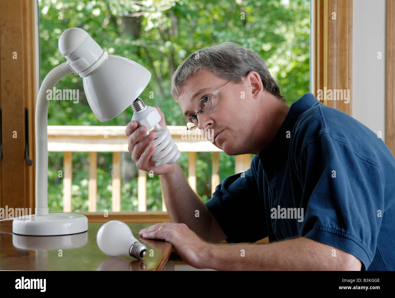 A 45 year old man replaces a household incandescent lightbulb with an energy saving compact fluorescent bulb - Stock Image