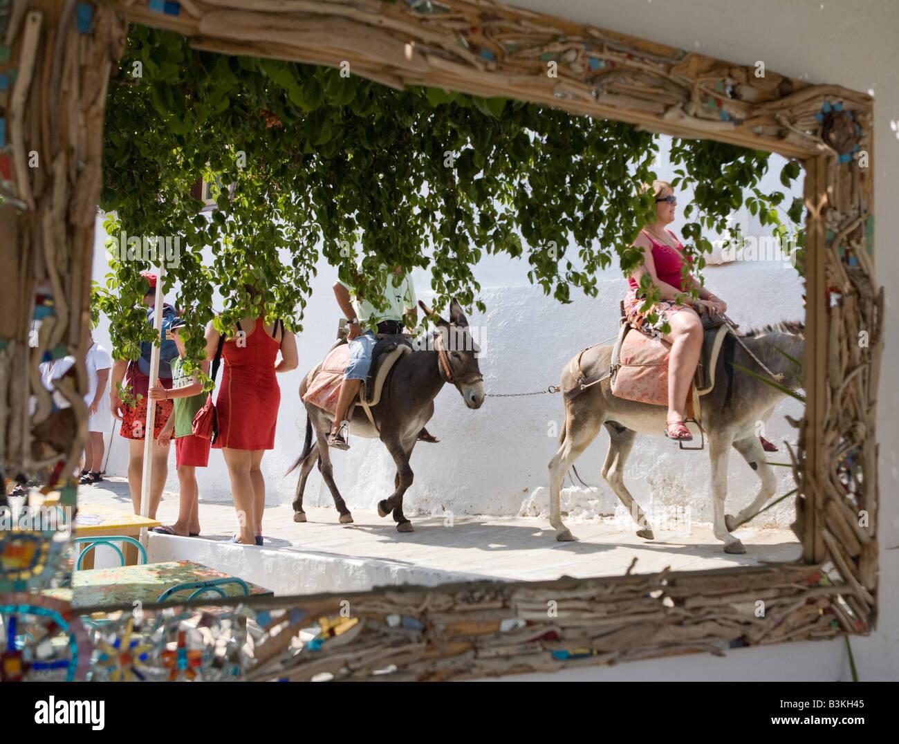 Mirror reflection of tourists riding donkeys, Lindos, Rhodes, Greece Stock Photo