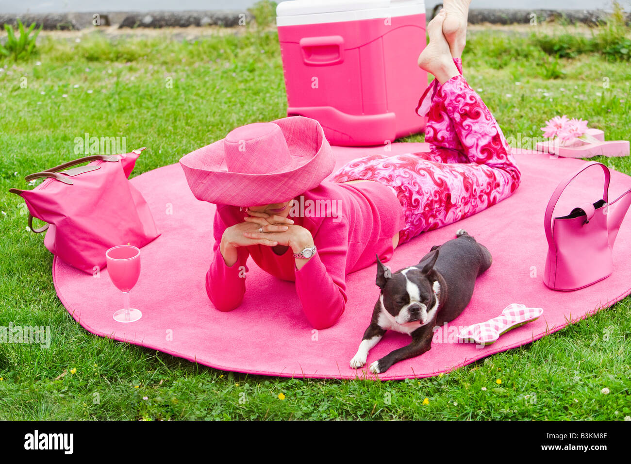 Woman in pink and dog picnicking - Stock Image
