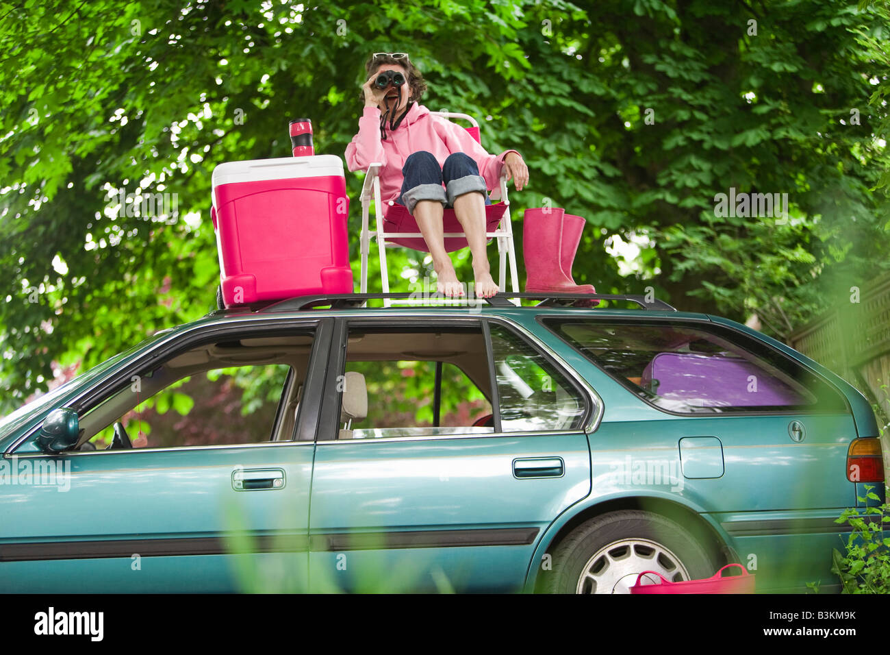 Woman with binoculars picnicking on top of car - Stock Image