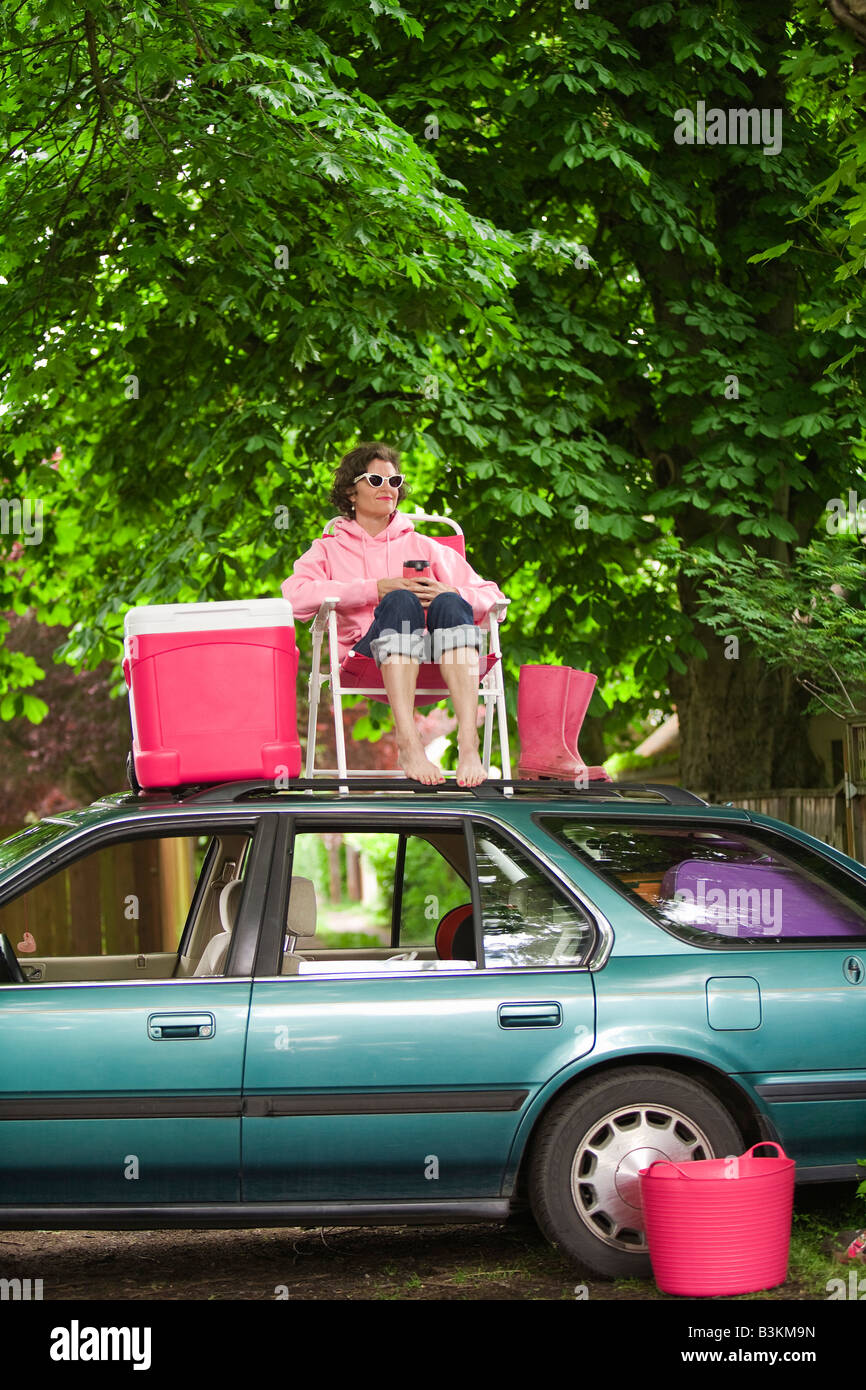 Woman picnicking on top of car - Stock Image