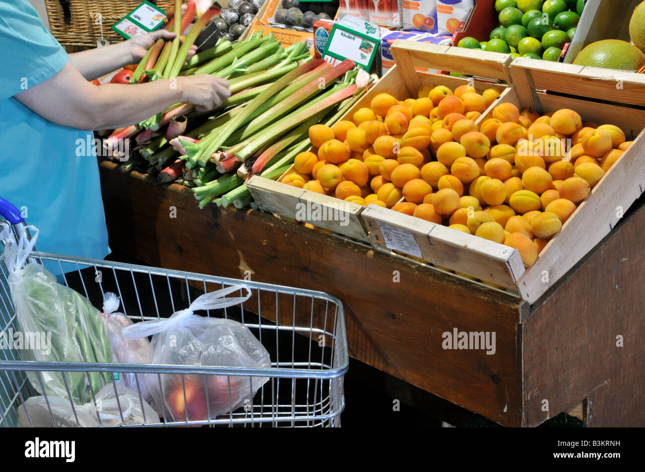 Interior of retail farm shop fruit produce on display woman shopper selecting rhubarb Stock Photo