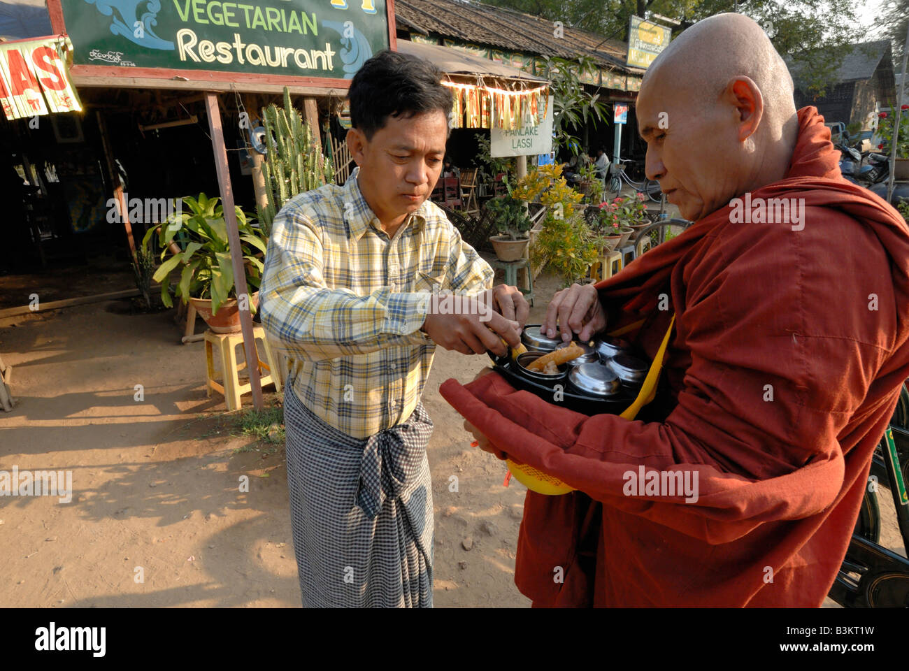 the Buddhist monk was going on a daily almsround (or pindacara) to collect food in Nyaung U township, Myanmar. Stock Photo