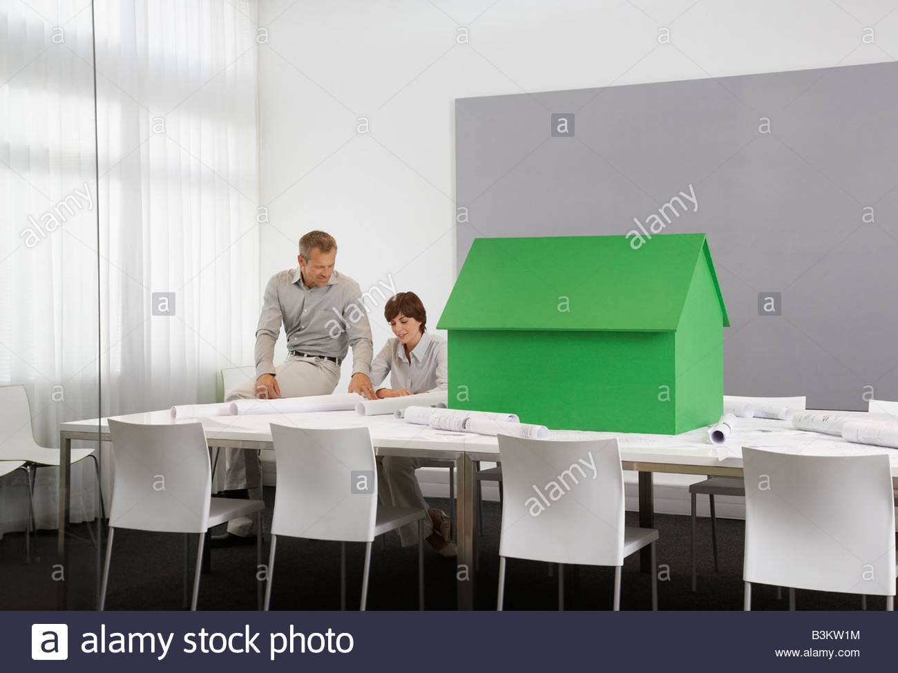 Business people with small model house on conference table - Stock Image