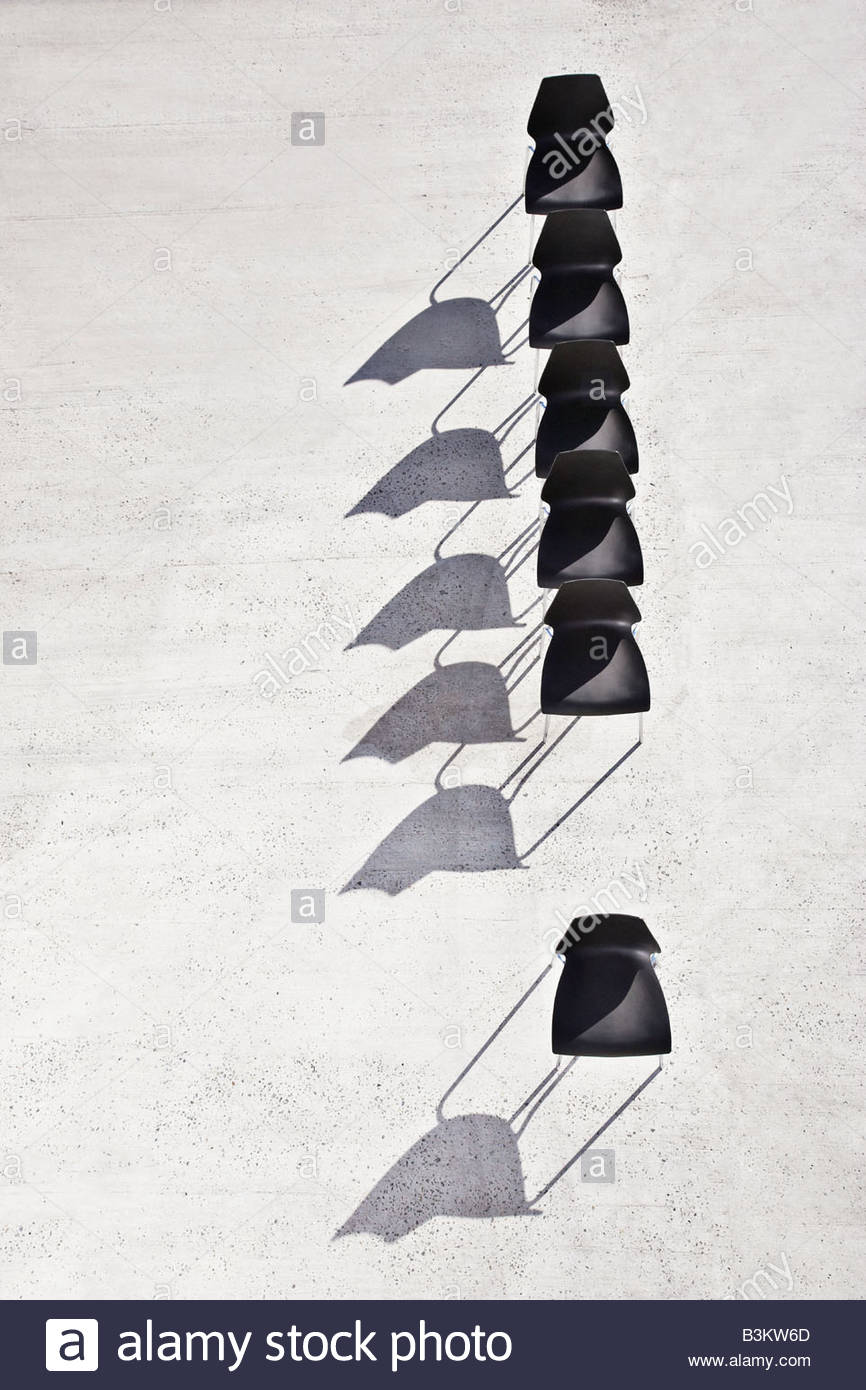 Single chair separated from line of office chairs - Stock Image