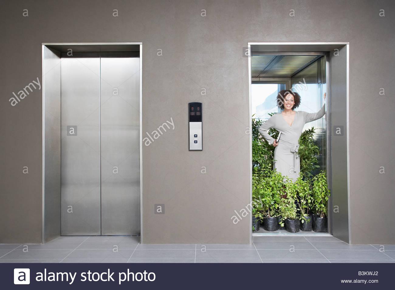 Businesswoman in elevator full of plants - Stock Image
