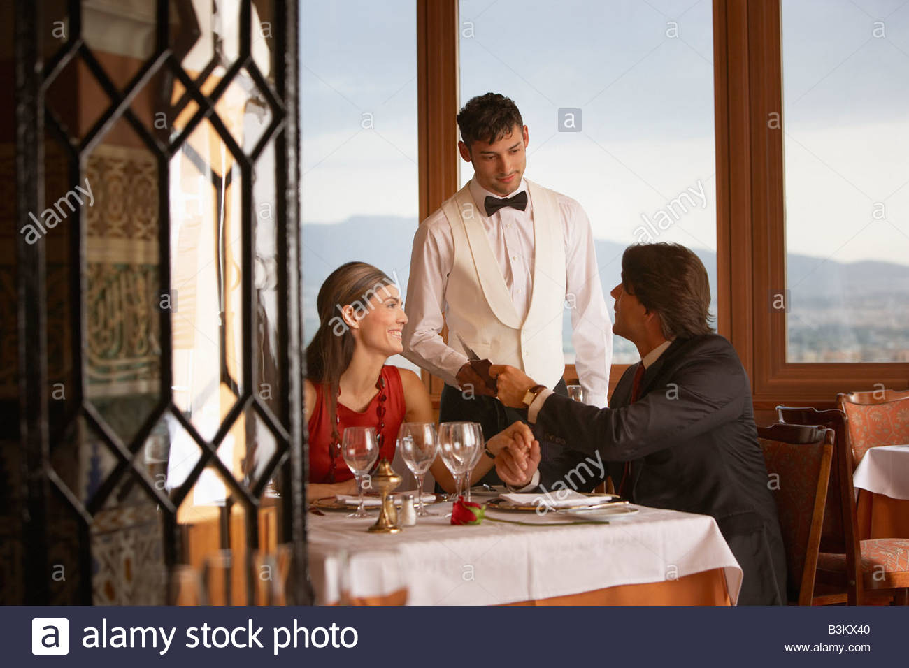 Waiter serving couple in elegant restaurant Stock Photo