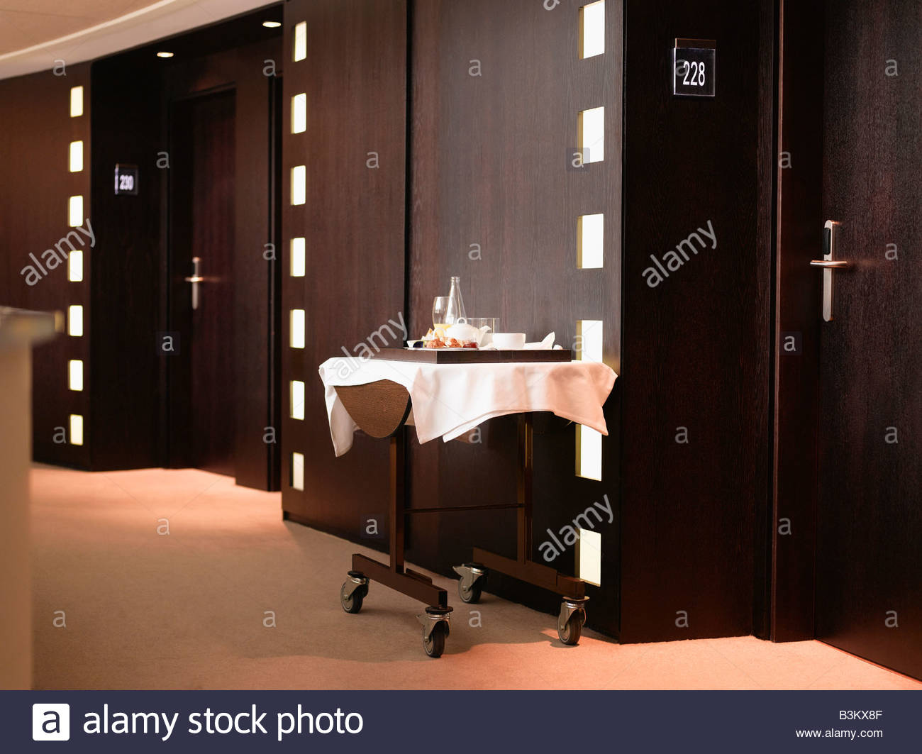 Discarded room service dishes in hotel corridor - Stock Image